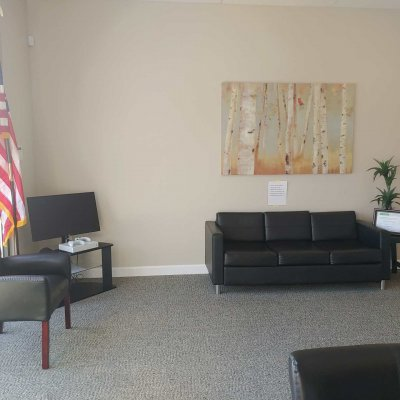 waiting area with a TV, xbox, sofa, chair, plant on a small table, artwork on the wall, and an American flag